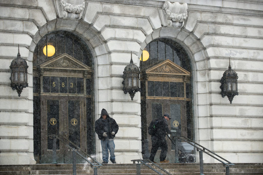 Two men spread salt on the steps of the Brennan Courthouse on Newark Avenue in Jersey City during a snowstorm on Monday, Jan. 26, 2015. Reena Rose Sibayan | The Jersey Journal